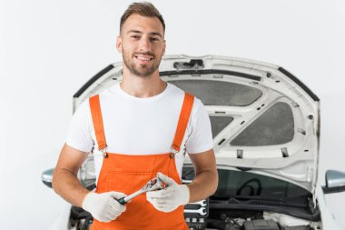 smiling handsome auto mechanic holding monkey wrench near car on white