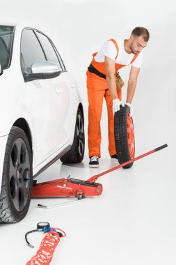 auto mechanic rolling car tire on white
