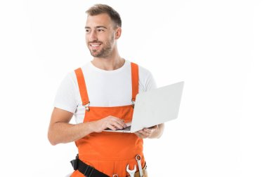 portrait of handsome auto mechanic in orange uniform holding laptop isolated on white