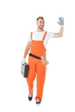 Handsome auto mechanic in orange uniform holding toolbox and waving hand isolated on white stock vector