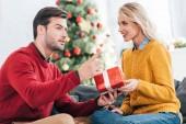 Fotografie šťastný mladý pár dárků představit doma s vánoční stromeček