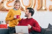 šťastný muž, pomocí přenosného počítače, zatímco žena držící šálek kávy doma s 2019 zlaté balónky pro nový rok