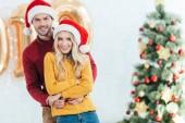 glückliches Paar in Weihnachtsmützen, das sich zu Hause mit Weihnachtsbaum umarmt
