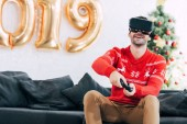 Fotografie Lächelnder Mann mit vr Headset und Steuerknüppel beim Videospiel im neuen Jahr 2019