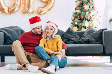smiling couple in santa hats hugging and sitting on floor at home with christmas tree