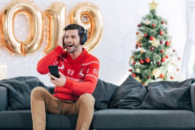 excited man listening music with headphones and smartphone on christmas eve
