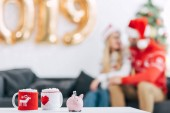 Fotografie selective focus of christmas coffee cups and piggy bank with banknote on table, couple sitting behind