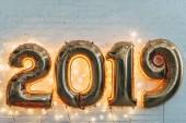 Fotografie 2019 zlaté balónky s světle věnec na bílé zdi pro nový rok