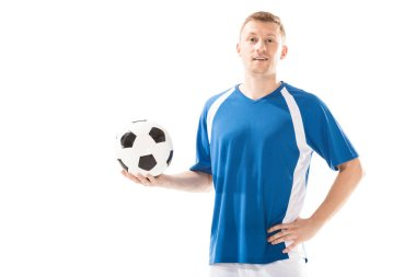 handsome young soccer player holding ball and smiling at camera isolated on white