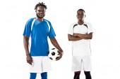 Fotografie sportovní mladé afroamerické fotbalistů se usmívá na fotoaparát izolované na bílém
