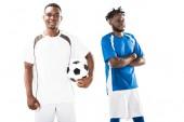 Fotografie šťastný mladý africký americký fotbalový hráč držení koule a usmívající se sportovec s překřížením rukou izolované na bílém