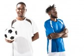 junger afrikanisch-amerikanischer Fußballer hält Ball und lächelt in die Kamera, während Sportler mit verschränkten Armen hinter ihm stehen