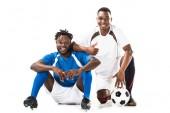 Fotografie Happy afrických amerických fotbalistů se usmívá na kameru a ukazuje palcem izolované na bílém