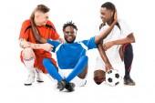 Fotografie šťastné mladé mnohonárodnostní fotbaloví hráči s míčem izolované na bílém