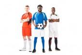 Fotografie po celé délce pohled mnohonárodnostní mladých fotbalistů, stáli a usmívá se na kameru izolované na bílém