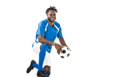 Cheerful young african american soccer player holding ball and smiling at camera isolated on white stock vector