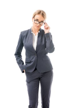attractive young businesswoman in stylish suit and eyeglasses looking at camera isolated on white