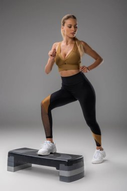 sportive young woman exercising on step board on grey