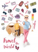 stylish kid in sunglasses showing thumb up while boy standing near cardboard car and traffic lights, with trip icons and travel the world lettering