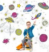 usmívající se školák směřující nahoru, zatímco sedí na hromadě knih s batohem, izolované na bílém s fantasy vesmíru, planety a kosmické lodě