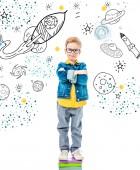 žák s překřížením rukou, stojící na hromadu knih, izolované na bílém s vesmíru, hvězdy a planety