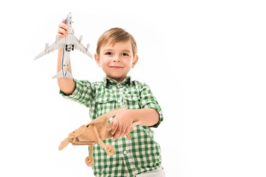 smiling little boy playing with toy planes isolated on white background