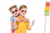 Fotografie stylish children in sunglasses, boy showing rock n roll signs, isolated on white with cardboard traffic lights on background