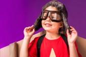 Fotografie usmívající se dítě s papírové letadlo křídla a ochranné brýle izolovaných na fialová