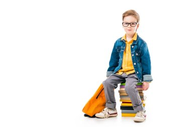 schoolboy sitting on pile of books with backpack, isolated on white