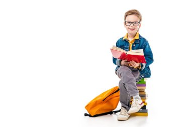 cheerful schoolboy reading book and sitting on pile of books with backpack, isolated on white