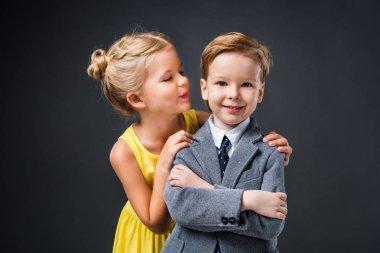 little stylish couple hugging and posing isolated on grey