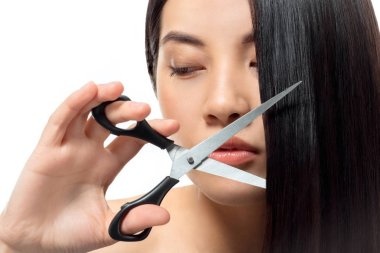 portrait of asian woman with scissors isolated on white, damaged hair and split ends concept