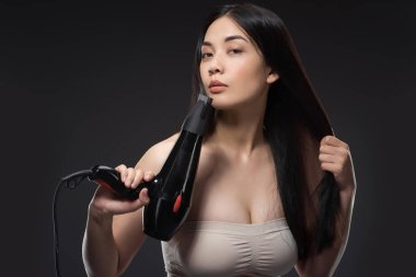 portrait of attractive asian woman with hair dryer isolated on black