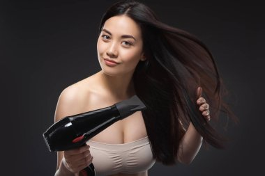 Portrait of beautiful asian woman with hair dryer isolated on black stock vector