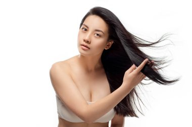 portrait of young asian woman with beautiful and healthy hair looking at camera isolated on white