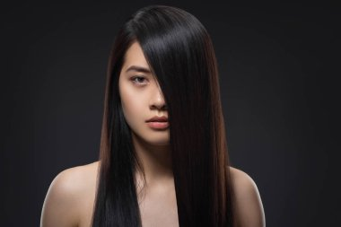 portrait of young asian woman with beautiful and healthy dark hair looking at camera isolated on black