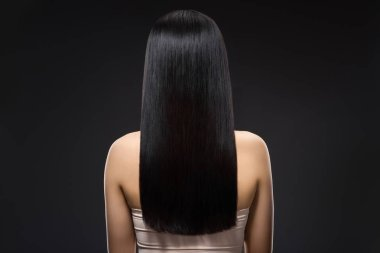 back view of woman with beautiful shiny hair isolated on black