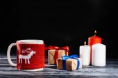 close-up view of cup, burning candles and christmas gifts on wooden table on black
