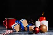 Nahaufnahme von brennenden Kerzen, Tannenzapfen, Weihnachtskugeln und Geschenke auf Holztisch auf schwarz
