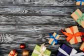 Fotografie pohled shora na vánoční dárky a lesklé cetky na dřevěný povrch