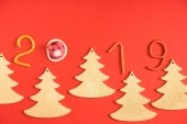 Fotografie top view of 2019 symbol, pig and fir trees on red