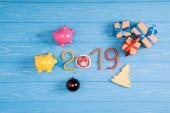 Fotografie pohled shora 2019 symbolu s růžové a žluté Prasátko Bank a vánoční dárky na modré dřevěný povrch