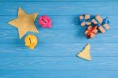 Fotografie pohled shora žluté a růžové Prasátko Bank, hvězda, vánoční stromek symbol a dárkové krabice modré dřevěné plochy