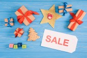 top view of sale sign, christmas presents and gingerbread cookie on blue wooden surface