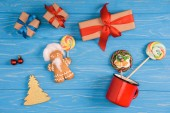 top view of gingerbread cookie, lollipops and christmas presents on blue wooden surface