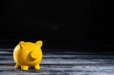 close-up view of yellow piggy bank on wooden table on black