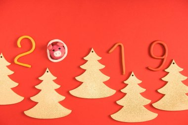 top view of 2019 symbol, pig and fir trees on red