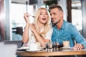 Fotografia ragazza che fa smorfie e alimentazione fidanzato con dessert dolce durante data nella caffetteria