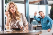 beautiful blonde woman eating dessert with flower in cafe, man gesturing to waiter on background
