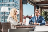 businesswoman with laptop having meeting with business partner in cafe